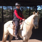 man in red sweater on a white horse