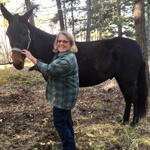 woman in a green shirt petting a horse